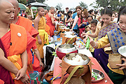 "Alms giving (tak bat) at That Luang festival, Vientiane, Lao PDR. Pha That Luang is the national symbol and most important religious monument of Laos. Vientiane's most important Theravada Buddhist festival, ""Boun That Luang"", is held here for three days during the full moon of the twelfth lunar month (November). Monks and laypeople from all over Laos congregate to celebrate the occasion with three days of religious ceremony followed by a week of festivities, day and night. The procession of laypeople begins at Wat Si Muang in the city centre and proceeds to Pha That Luang to make offerings to the monks in order to accumulate merit for rebirth into a better life. The religious part concludes as laypeople, carrying incense and candles as offerings, circumambulate Pha That Luang three times in honor of Buddha."