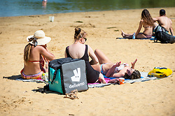 © Licensed to London News Pictures. 14/06/2021. LONDON, UK.  People with a Deliveroo delivery sunbathe on the beach at Ruislip Lido in north west London.   The forecast is for the temperature to rise to 28C, the hottest day of the year so far.  Photo credit: Stephen Chung/LNP