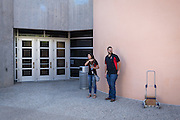 Monica Nezzer and Patrick Arite wait in the shade for the group of prospective students they are to give a tour on Thursday June 2, 2016. Nezzer and Arite are both students at the University of New Mexico and are working 15-30 hours per week giving campus tours in order to help put themselves through college. (Steven St. John for NPR)