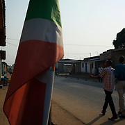 People walk by a Burundi national flag in Cibitoke neighbourhood in Bujumbura. Cibitoke have in the past couple of moths been the scene of violent protests against the presidents third term bid.