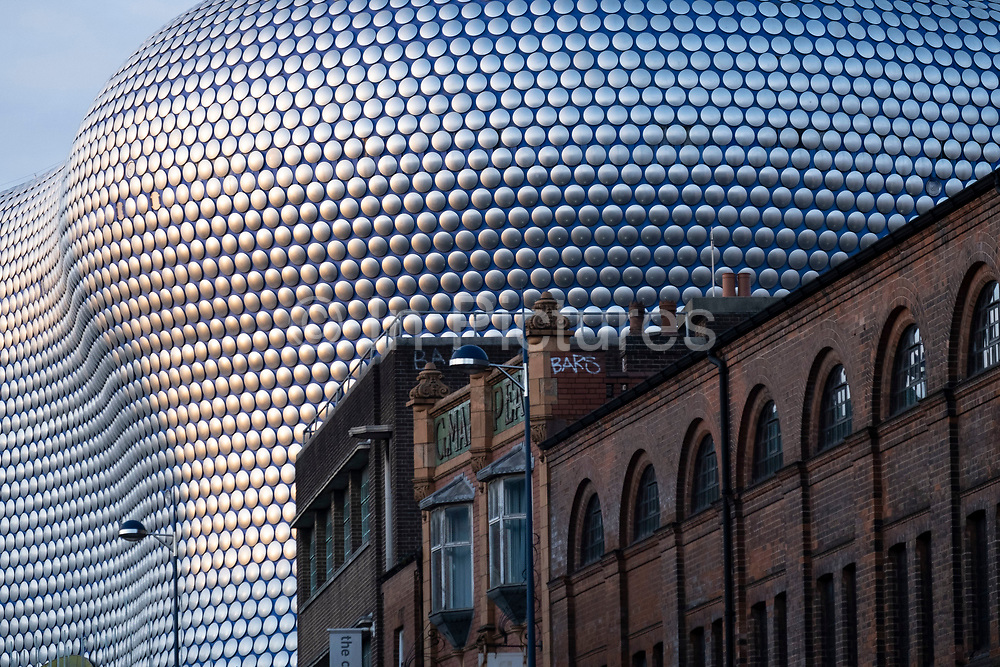 Modern landmark architecture of the Selfridges Building near to old red brick industrial buildings on 7th January 2021 in Birmingham, United Kingdom. The building is part of the Bullring Shopping Centre and houses Selfridges Department Store. The building was completed in 2003 at a cost of £60 million and designed by architecture firm Future Systems. It has a steel framework with sprayed concrete facade. Since its construction, the building has become an iconic architectural landmark and seen as a major contribution to the regeneration of Birmingham.
