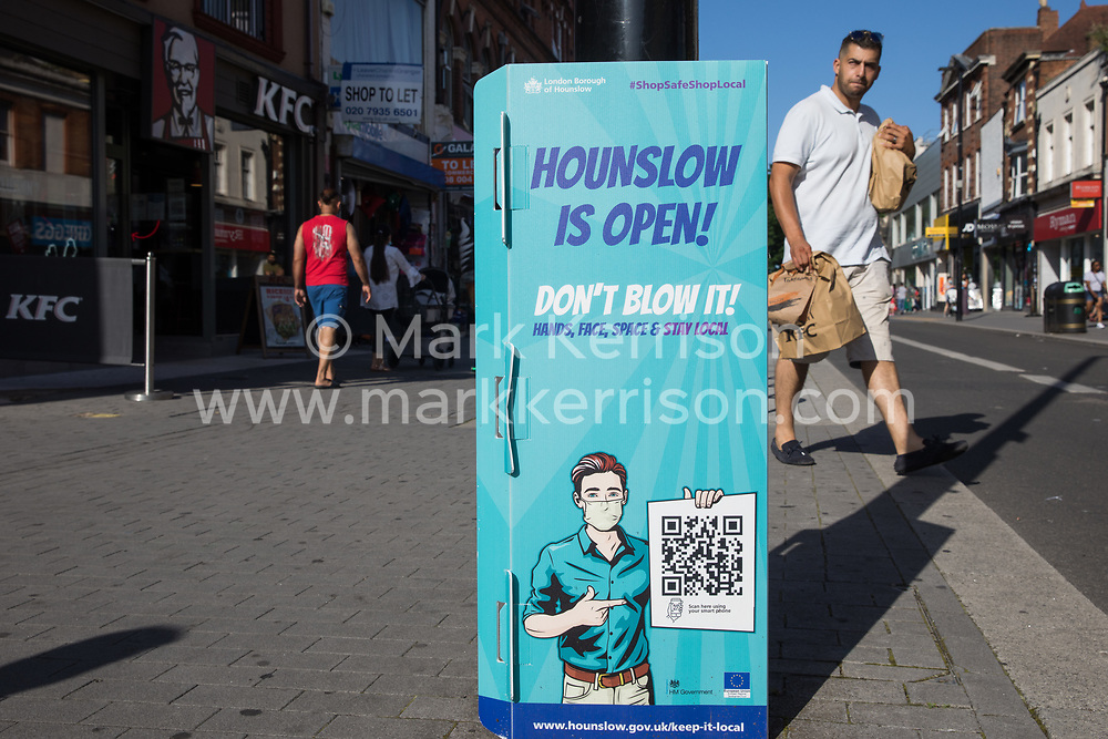 A member of the public passes a London Borough of Hounslow Covid-19 public information sign urging residents to take precautions to minimise the spread of the coronavirus amid rising concern regarding the Delta variant on 17th July 2021 in Hounslow, United Kingdom. The UK government is currently still expected to lift almost all restrictions on social contact on 19th July, known as 'Freedom Day', but the current wave driven by the Delta variant is not expected to peak until mid-August.