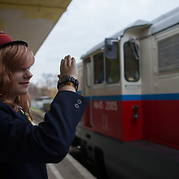 Girl working at the station salutes to the train after signaling it can leave the station of the Children's Railway in the Buda Hills in Budapest, Hungary on November 13, 2014. ATTILA VOLGYI
