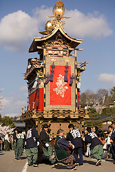 Asia, Japan, Gifu prefecture, Takayama (also known as Hida-Takayama), men pull elaborate festival float (yatai)  through streets in Gonjunko Procession during Sanno Festival of Hie Jinja Shrine, held annually in April.