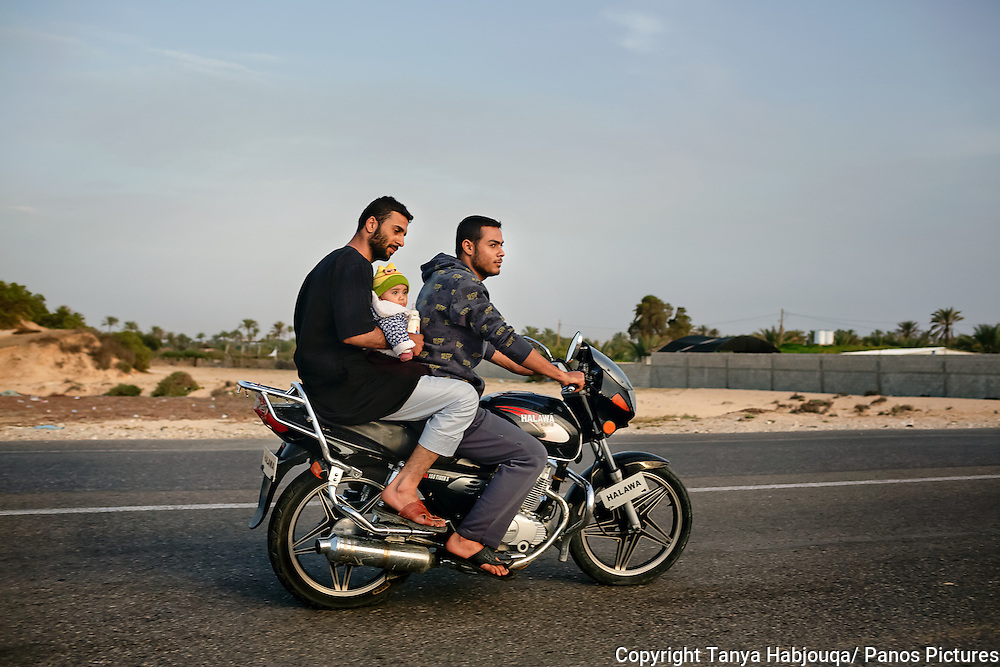 Father, baby, bottle and uncle go for a motorcycle ride on the Gaza Beach Highway.