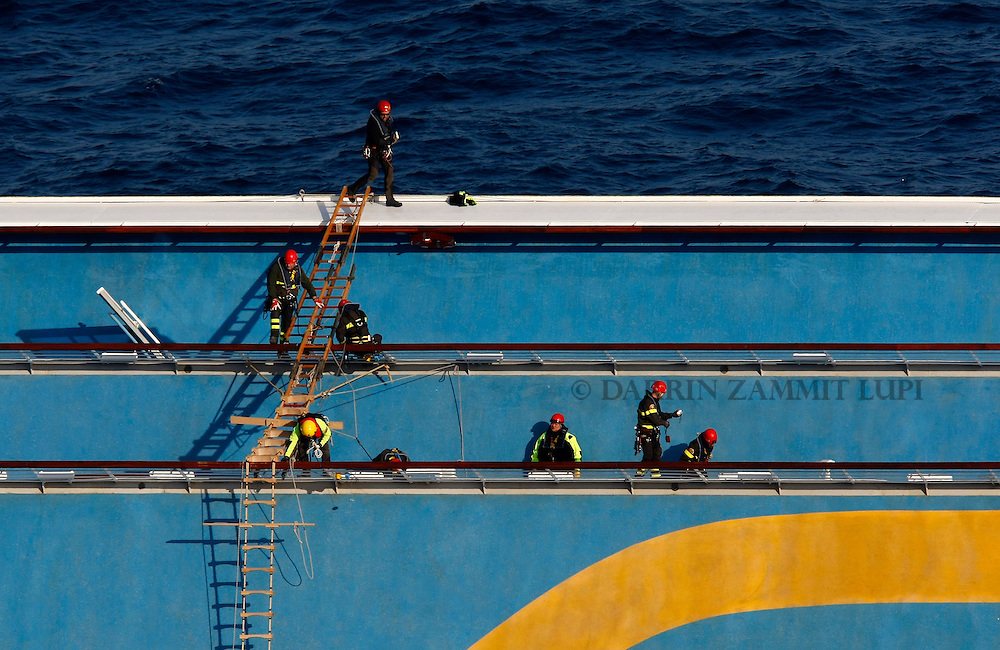 Firefighter rescuers climb along the decks on the cruise liner Costa Concordia off the west coast of Italy at Giglio island January 30, 2012. Search operations at the Costa Concordia resumed on Monday after being suspended for a day due to weather conditions and some movement of the capsized cruise ship...REUTERS/Darrin Zammit Lupi (ITALY)