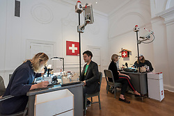 "© Licensed to London News Pictures. 05/10/2018. LONDON, UK. Visitors have passports issued by the artist's assistants Preview of ""Swiss Passport Office"" by American artist Tom Sachs at Galerie Thaddaeus Ropac in Mayfair.  To coincide with Frieze Week, the gallery will remain open for 24 hours from 6pm 5 October to 6pm 7 October for the issuing of serial-numbered Tom Sachs Swiss passports for visitors.  The installation reflects the concerns relating to Brexit, Syria and Donald Trump's immigration policies and challenges the notion of global citizenship.  Photo credit: Stephen Chung/LNP"