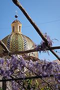 The dome of Santa Maria Assunta, the main church in Positano, rises over a trellised walkway covered in lavender flowers. Positano, Amalafi Coast, Campagna, Italy.
