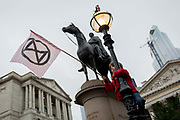 A young environmental activist protests about Climate Change beneath the statue of the Duke of Wellington during the blockade at the junction at Bank outside the Bank of England in the heart of the capitals financial district, the City of London aka the Square Mile, on the seventh day of a two-week prolonged worldwide protest by members of Extinction Rebellion, on 14th October 2019, in London, England.