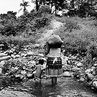 A mother and child displaced by recent violence in their village on the river bank where the womenfolk do their laundry, Saravena, Aruaca.<br />