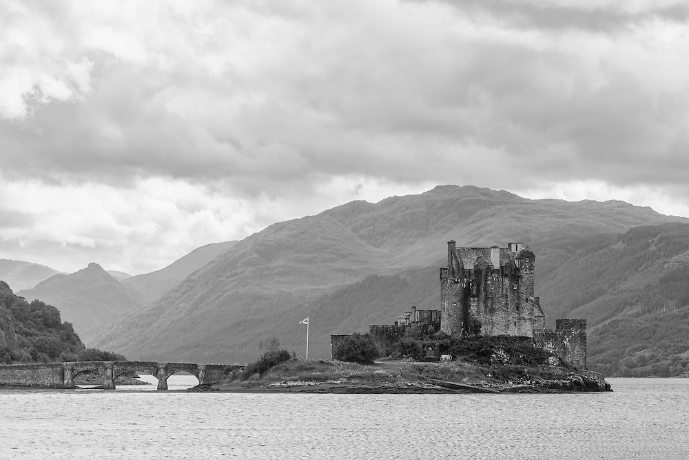 Eilean Donan offers one of the most iconic images of Scotland. It is situated on an island at the point where three great sea lochs meet, and surrounded by some majestic scenery.<br /> <br /> First inhabited around the 6th century, the first fortified castle was built in the mid 13th century and stood guard over the lands of Kintail. Since then, at least four different versions of the castle have been built and re-built as the feudal history of Scotland unfolded through the centuries.<br /> <br /> Partially destroyed in a Jacobite uprising in 1719, Eilean Donan lay in ruins for the best part of 200 years until Lieutenant Colonel John MacRae-Gilstrap bought the island in 1911 and proceeded to restore the castle to its former glory. After 20 years of toil and labour the castle was re-opened in 1932.<br /> <br /> This photograph is a monochromatic close view of Eilean Donan Castle from the north, on Loch Alsh through to Loch Duich. The photograph can be purchased as print, mounted print in frames, canvas or aluminum or as a digital file.