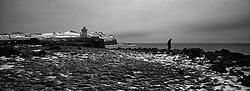 Man fighting against the storm with a lighthouse in the back. From the island Grimsey, north of Iceland / Maður berst á móti storminum með vitann í Grímsey í baksýn