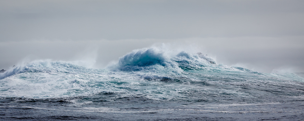 Panoramic view of crashing blue wave and turbulent ocean waters