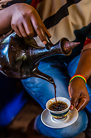 Woman pouring Ethiopian coffee from a jabena. The jebena is a container used to brew coffee in the Eritrean and Ethiopian traditional coffee ceremony.