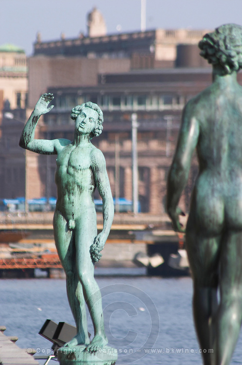 In the Garden of Stadshuset, the Stockholm Town Hall. two bronze statues: Song by Carl Eldh a naked man holding a bunch of grapes and of a naked woman by Carl Eldh Stockholm, Sweden, Sverige, Europe