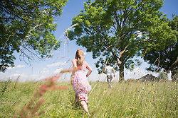 Rear view of mid adult couple running through grass on meadow in the countryside, Bavaria, Germany