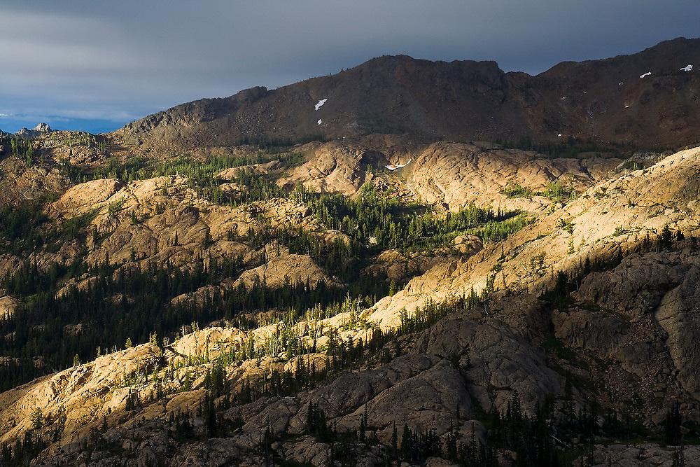 Swaths of light illuminate exposed bedrock and larch trees near Ingalls Lake, Alpine Lakes Wilderness, Washington.