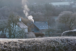 © Licensed to London News Pictures. 02/01/2019. Builth Wells, Powys, Wales, UK. Smoke rises from a chimney near Builth Wells oin Powys. Temperatures dropped overnight to minus 3.5 degrees centigrade in Powys, Wales, UK. credit: Graham M. Lawrence/LNP