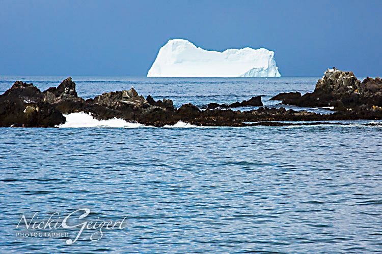 Large iceberg in the distance at sea with blue water and rocks, Antarctica. Landscape and Nature photography wall art, fine art photography prints, stock images.