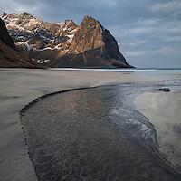Mountain peaks rise over Kvalvika beach, Moskenesøy, Lofoten Islands, Norway