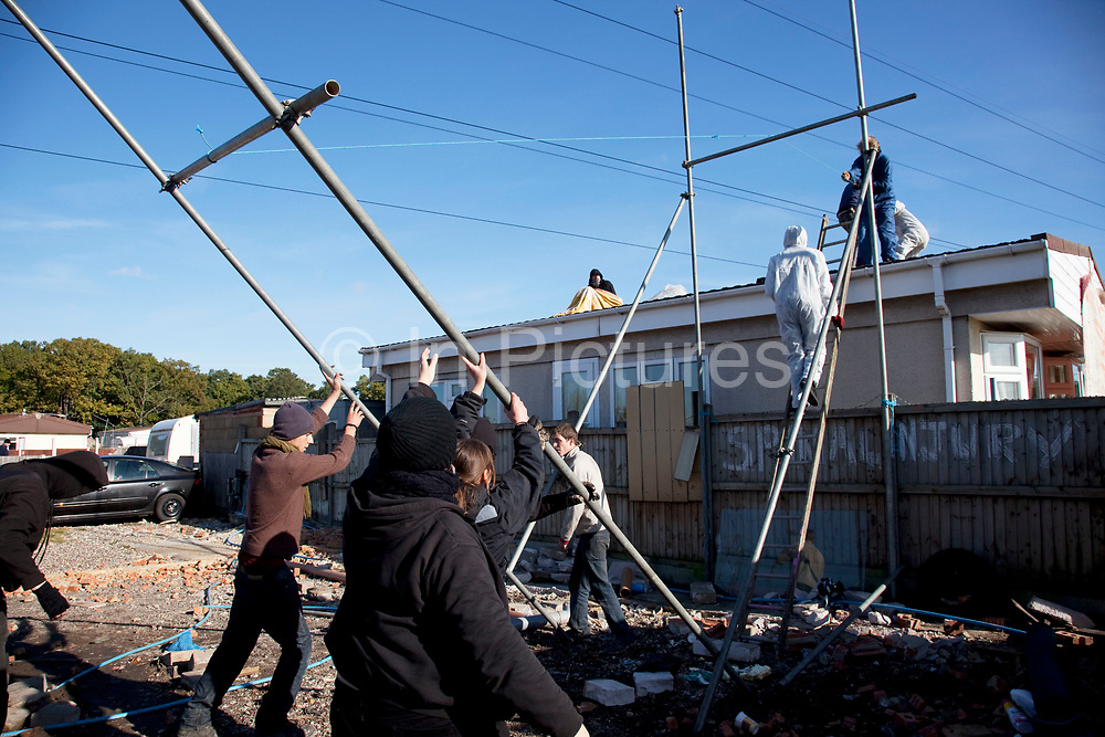 Protesters erect a new scaffolding tower. Travellers at Dale Farm site prior to eviction. Riot police and bailiffs were present on 20th October 2011, as the site was cleared of the last protesters chained to barricades. Dale Farm is part of a Romany Gypsy and Irish Traveller site in Crays Hill, Essex, UK<br /> <br /> Dale Farm housed over 1,000 people, the largest Traveller concentration in the UK. The whole of the site is owned by residents and is located within the Green Belt. It is in two parts: in one, residents constructed buildings with planning permission to do so; in the other, residents were refused planning permission due to the green belt policy, and built on the site anyway.