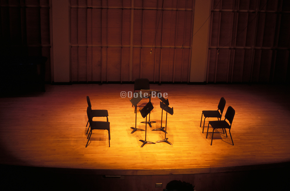 empty chairs and music sheet stands on stage