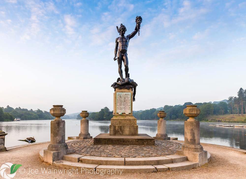 A replica of the statue of Perseus and Medusa by sculptor Benevenuto Cellini at Trentham Gardens, Staffordshire - with the lake at Capability Brown landscape in the background