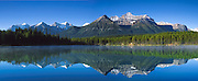 "Herbert Lake reflects peaks in Banff National Park, Alberta, Canada. Banff is part of the Canadian Rocky Mountain Parks World Heritage Site declared by UNESCO in 1984. Panorama stitched from 3 images shot on film. Published on the cover of John Steel Rail Tours corporate brochure 2006, www.johnsteel.com. Published in ""Light Travel: Photography on the Go"" book by Tom Dempsey 2009, 2010."
