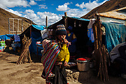 A girl carries a baby on her back during the festivity of the Lord of Qoyllur Rit'i, in tents merchants sell food to the pilgrims in Cusco, Peru.