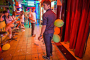 "12 JANUARY 2013 - BANGKOK, THAILAND:  Workers in a Nana Entertainment Plaza go-go bar relax in the hallway in front of the bar. Prostitution in Thailand is illegal, although in practice it is tolerated and partly regulated. Prostitution is practiced openly throughout the country. The number of prostitutes is difficult to determine, estimates vary widely. Since the Vietnam War, Thailand has gained international notoriety among travelers from many countries as a sex tourism destination. One estimate published in 2003 placed the trade at US$ 4.3 billion per year or about three percent of the Thai economy. It has been suggested that at least 10% of tourist dollars may be spent on the sex trade. According to a 2001 report by the World Health Organisation: ""There are between 150,000 and 200,000 sex workers (in Thailand).""    PHOTO BY JACK KURTZ"