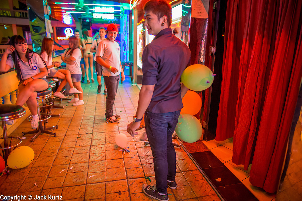 """12 JANUARY 2013 - BANGKOK, THAILAND:  Workers in a Nana Entertainment Plaza go-go bar relax in the hallway in front of the bar. Prostitution in Thailand is illegal, although in practice it is tolerated and partly regulated. Prostitution is practiced openly throughout the country. The number of prostitutes is difficult to determine, estimates vary widely. Since the Vietnam War, Thailand has gained international notoriety among travelers from many countries as a sex tourism destination. One estimate published in 2003 placed the trade at US$ 4.3 billion per year or about three percent of the Thai economy. It has been suggested that at least 10% of tourist dollars may be spent on the sex trade. According to a 2001 report by the World Health Organisation: """"There are between 150,000 and 200,000 sex workers (in Thailand).""""    PHOTO BY JACK KURTZ"""