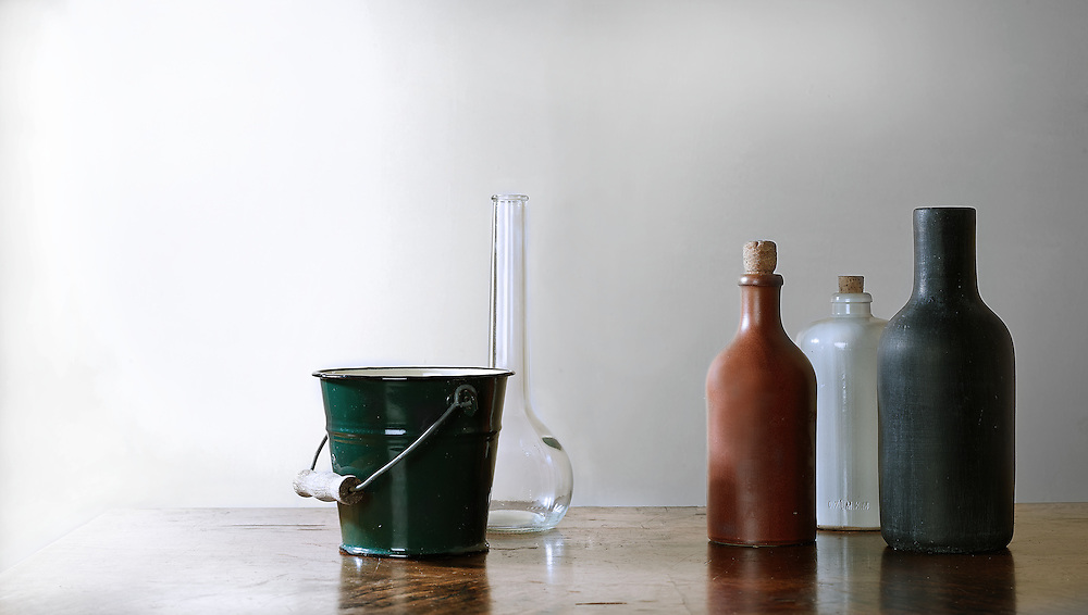 still life studies with bottles and a vase and a bucket