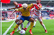 Lyle Taylor of Charlton Athletic (9) holds up the ball in the corner up against Herbie Kane of Doncaster Rovers (15) and Alfie May of Doncaster Rovers (19) during the EFL Sky Bet League 1 play off first leg match between Doncaster Rovers and Charlton Athletic at the Keepmoat Stadium, Doncaster, England on 12 May 2019.