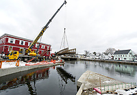 Crane and crew workers lift the metal footbridge to its resting place at Perley Canal and Jewett Brook connecting the river walk through downtown Laconia Thursday morning.  (Karen Bobotas/for the Laconia Daily Sun)