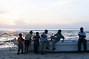 A group of young boys walk along Kizimkaze Beach at sunset in the south of the island on 9th December 2008 in Zanzibar, Tanzania. Zanzibar is a small island just off the coast of the Tanzanian mainland in the Indian Ocean. In part due to its name, Zanzibar is a travel destination of mystical reputation, known for its incredible sealife on its many reefs, the powder white coral sand beaches and the traditional cultivation of spices.