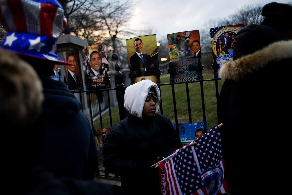 Obama Inauguration - Monday activities around the Capitol on Martin Luther King Jr. Day. A young vendor sells Obama-themed merchandise and flags at dusk near the White House.