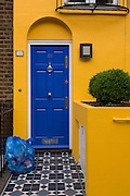 Yellow house with blue door and blue recycling bags on front doorstep, London.