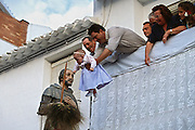 A family holds down infant from balcony to a sculpture of the town's patron saint, San Isidro, for good luck at the Fiesta de San Isidro in Periana, Spain.