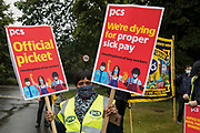 A PCS member holds two placards at a picket outside the Old Police House in Hyde Park for Royal Parks workers outsourced via French multinational VINCI Facilities as part of joint strike action by the United Voices of the World UVW and Public and Commercial Services PCS trade unions on 30th July 2021 in London, United Kingdom. The joint strike, with members dual carding over pay, conditions and the sacking of a member of staff, is believed to be the first between a TUC and a non-TUC trade union and follows the launch of a legal challenge by the Royal Parks workers against indirect racial discrimination by the Royal Parks.