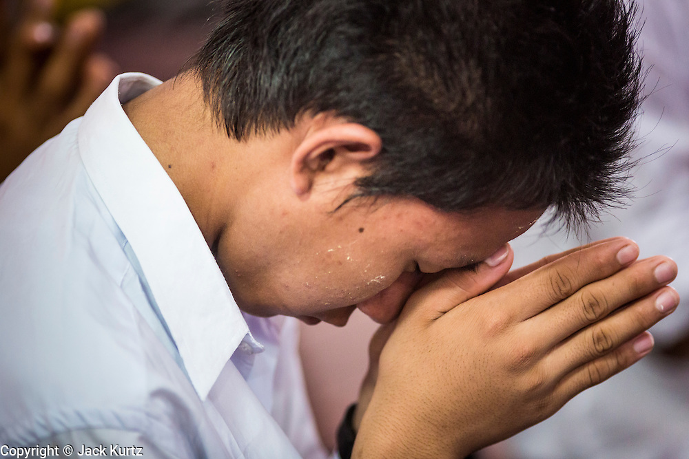 24 MAY 2013 - MAE SOT, THAILAND: A Burmese man prays in Wat Pha Mai during Visakha Puja Day services. Visakha Puja (Vesak) marks three important events in the Buddha's life: his birth, his attainment of enlightenment and his death. It is celebrated on the full moon of the sixth lunar month, usually in May on the Gregorian calendar. This year it is on May 24 in Thailand and Myanmar. It is celebrated throughout the Buddhist world and is considered one of the holiest Buddhist holidays. Burmese Buddhist in Mae Sot celebrated with a procession through Mae Sot that ended with a service followed by a communal meal at Wat Pha Mai, the most important Burmese Buddhist temple in Mae Sot.     PHOTO BY JACK KURTZ