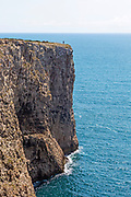 Sheer cliffs rise from Atlantic Ocean at Cabo de São Vicente, Cape St Vincent, Algarve, Portugal with one person standing on top near the edge