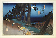 Mochizuki: Full Moon. From 'The Sixty-nine Stations of the Kisokaido Road'  1832-1834. Coloured woodblock print.  Porters and pack animals transport goods along a road lined with pine trees. Ando Hiroshige  also called Ando Tokutaro (1797-1858) Japanese artist and printmaker.