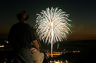 A family watches the Town of Woodbury fireworks display from the Route 6 overlook in Central Valley, N.Y..July 3, 2004.