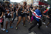 Dancers behind a sound system dance together in time on Monday 28th August 2016 at the 50th Notting Hill Carnival in West London. A celebration of West Indian / Caribbean culture and Europes largest street party, festival and parade. Revellers come in their hundreds of thousands to have fun, dance, drink and let go in the brilliant atmosphere. It is led by members of the West Indian / Caribbean community, particularly the Trinidadian and Tobagonian British population, many of whom have lived in the area since the 1950s. The carnival has attracted up to 2 million people in the past and centres around a parade of floats, dancers and sound systems.