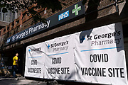 Days before the UK governments widespread re-opening of Covid pandamic restrictions Monday 19th July aka Freedom Day, the number of daily infections has risen to 50,000, and St Georges NHS Pharmacy at Elephant And castle displays its banners to encourage those elegible to have their vaccinations, on 16th July 2021, in London, England.