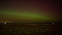 © Licensed to London News Pictures. 27/02/2014<br /> <br /> Saltburn, England<br /> <br /> The Aurora Borealis is visible out to sea in Saltburn by the Sea in Cleveland as ships make their way into Teesport.<br /> <br /> Photo credit : Ian Forsyth/LNP