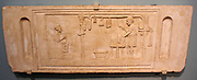 Funerary relief for butcher, AD125-150.  A butcher is at work in his shop; various cuts of meat hang above; his seated wife holds a wax tablet; she goes the shop's accounts.  She wears a fashionable hairstyle of the Hadrianic period.  The relief was probably set in the facade of a tomb.