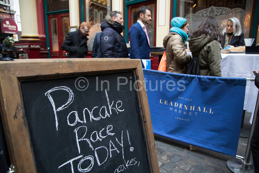 Free pancakes on Shrove Tuesday as festivities warm up for the Leadenhall Market Pancake Day Race on 13th February 2018 in London, United Kingdom. Competing teams of City workers outside The Lamb Tavern tackle the 25m course, competing to win the coveted frying pan trophy as they flip their wayaround the historic 14th century market.
