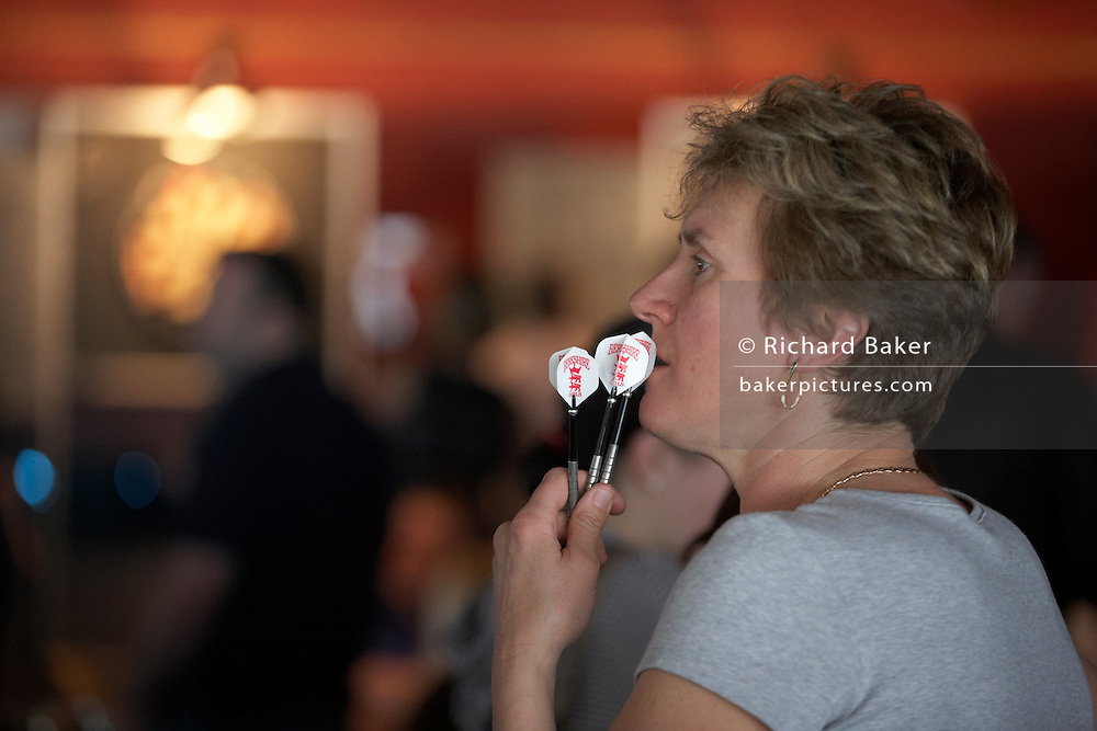 A female darts player is in deep thought as she prepares for her next game during ladies darts tournament