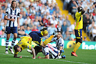 Sunderland's Steven Fletcher falls awkwardly and has to leave the field injured. Barclays Premier league match, West Bromwich Albion v Sunderland at the Hawthorns in West Bromwich, England on Sat 21st Sept 2013. pic by Andrew Orchard, Andrew Orchard sports photography,